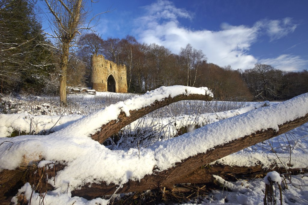 England, West Yorkshire, Leeds. Snow covering the ground around the castle in Roundhay Park, one of the biggest city parks in Europe. The castle is a 19th century folly built by George Nettleton. : Stock Photo
