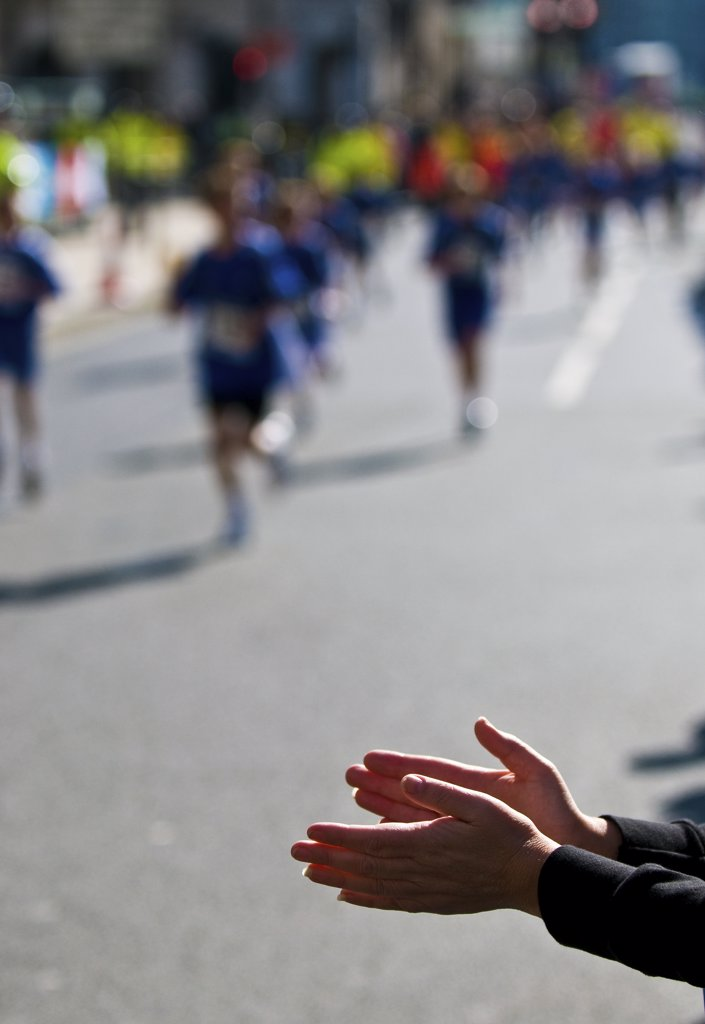 Stock Photo: 4282-8495 England, London. A spectator applauding runners taking part in the London Marathon.