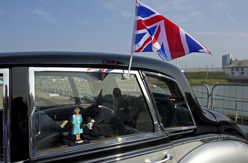 Stock Photo: 4282-8556 England, Kent, Chatham. A small figure of Queen Elizabeth ll in the window of a classic car and a union flag fixed to the outside.