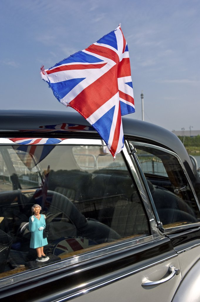 Stock Photo: 4282-8557 England, Kent, Chatham. A small figure of Queen Elizabeth ll in the window of a classic car and a union flag fixed to the outside.