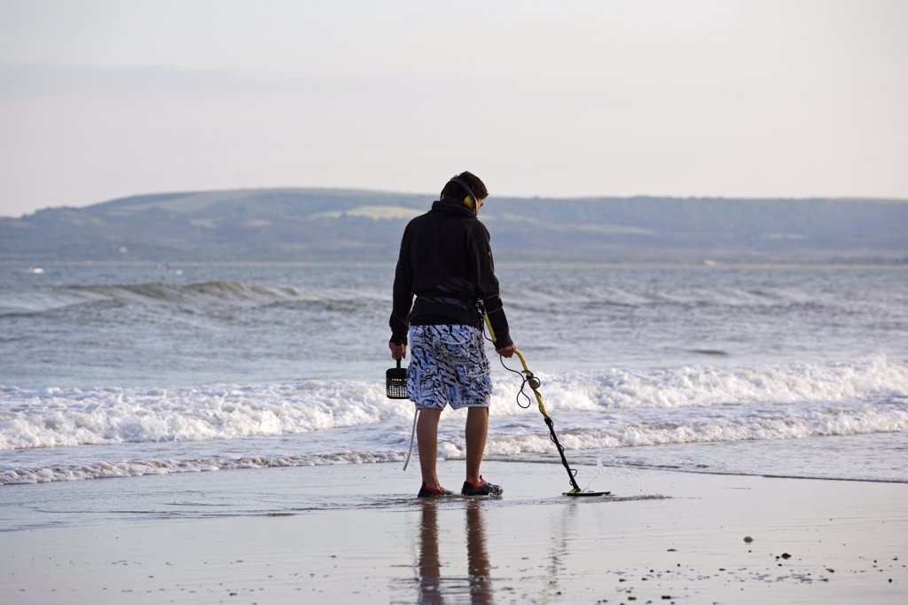 England, Dorset, Bournemouth. A man metal detecting on the seashore at Bournemouth. : Stock Photo