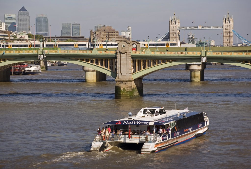 Stock Photo: 4282-9116 England, London, Southwark Bridge. A Thames Clipper boat heading east towards the City of London, Southwark Bridge and Tower Bridge.