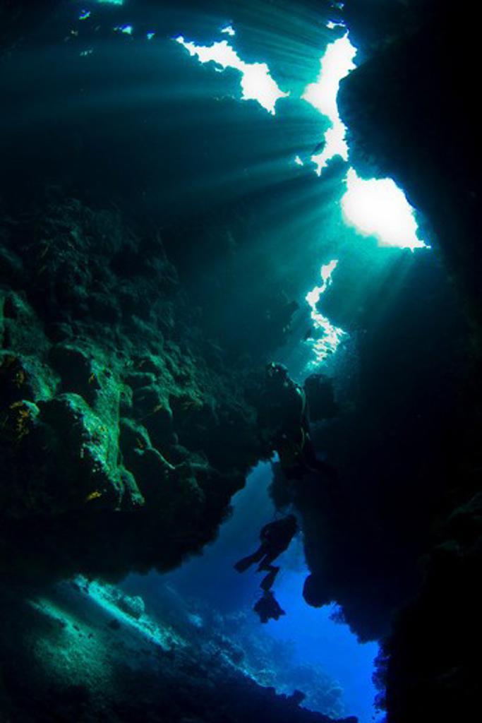 Scuba diver near sea cave underwater : Stock Photo