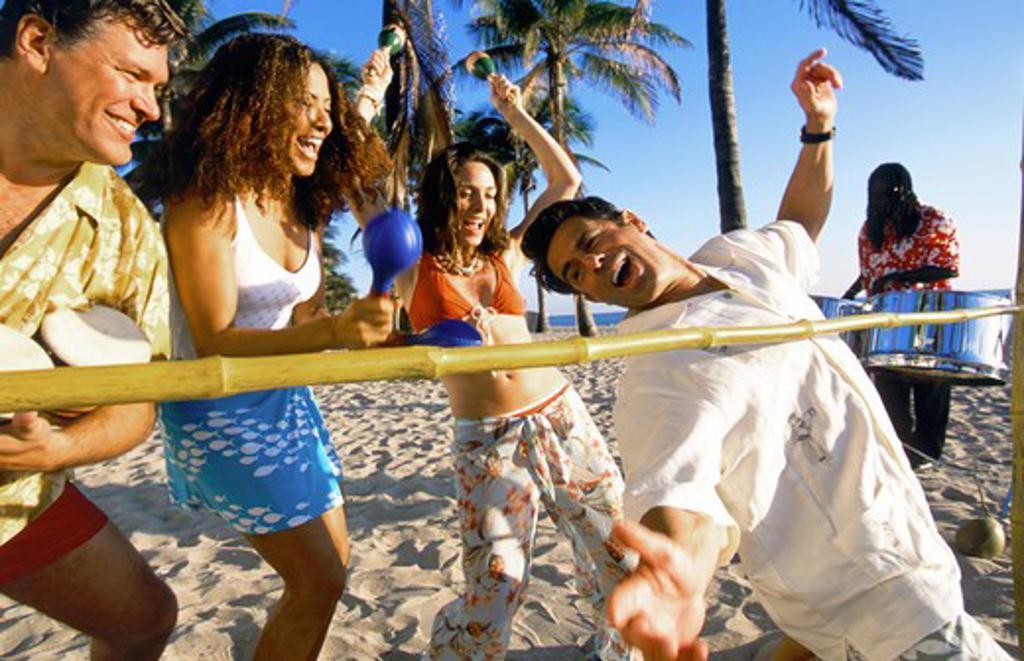 Vacationers doing the limbo. : Stock Photo