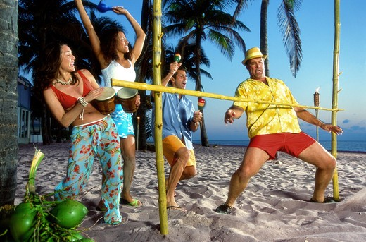 Vacationers have fun doing the limbo. : Stock Photo
