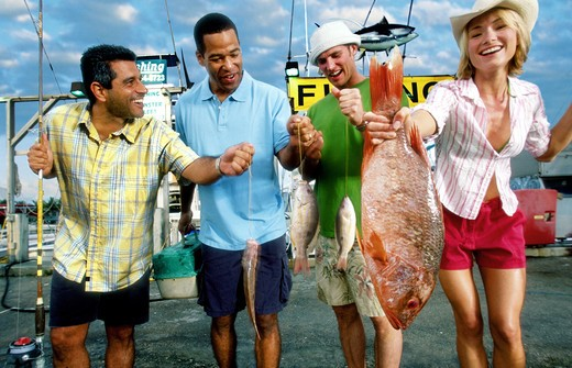 Stock Photo: 4285-1049 Woman shows up the men in deep sea fishing.