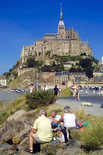 PEOPLE PICNICING AND MONT-ST-MICHEL NORMANDY FRANCE : Stock Photo