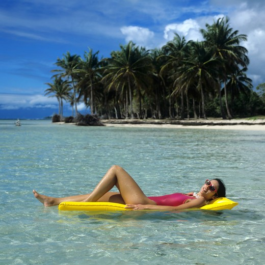 Stock Photo: 4285-10555 MR YOUNG WOMAN IN RED SWIMSUIT FLOATING AND SUNBATHING ON YELLOW RAFT LAGOON SEA PALM TREES BEACH GUADELOUPE FRENCH WEST INDIES