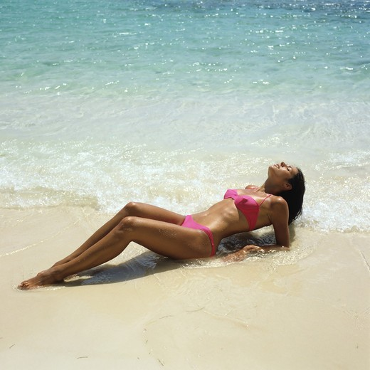 Stock Photo: 4285-10577 MR YOUNG WOMAN WITH A PINK BIKINI SUNBATHING ON BEACH SEA GUADELOUPE FRENCH WEST INDIES