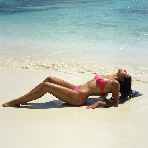 Stock Photo: 4285-10578 MR YOUNG WOMAN WITH A PINK BIKINI SUNBATHING ON BEACH SEA GUADELOUPE FRENCH WEST INDIES