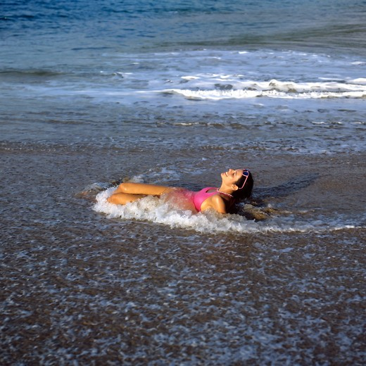 MR YOUNG WOMAN WITH A PINK SWIMSUIT RELAXING IN SHALLOW SEA WATER AND WAVES ON BEACH GUADELOUPE FRENCH WEST INDIES : Stock Photo