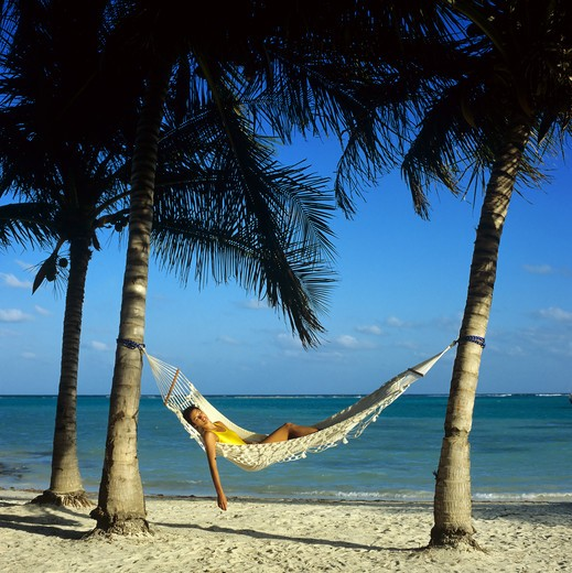 Stock Photo: 4285-10628 MR YOUNG WOMAN IN YELLOW SWIMSUIT SLEEPING IN HAMMOCK BEACH SEA PALM TREES GUADELOUPE FRENCH WEST INDIES