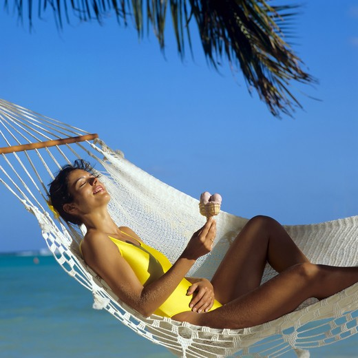 MR YOUNG WOMAN IN YELLOW SWIMSUIT HOLDING AN ICE-CREAM CONE AND RELAXING IN HAMMOCK SEA PALM TREE GUADELOUPE FRENCH WEST INDIES : Stock Photo