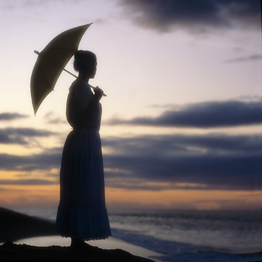 Stock Photo: 4285-10653 MR YOUNG WOMAN'S SILHOUETTE HOLDING AN UMBRELLA ON THE BEACH AT SUNSET SEA GUADELOUPE FRENCH WEST INDIES