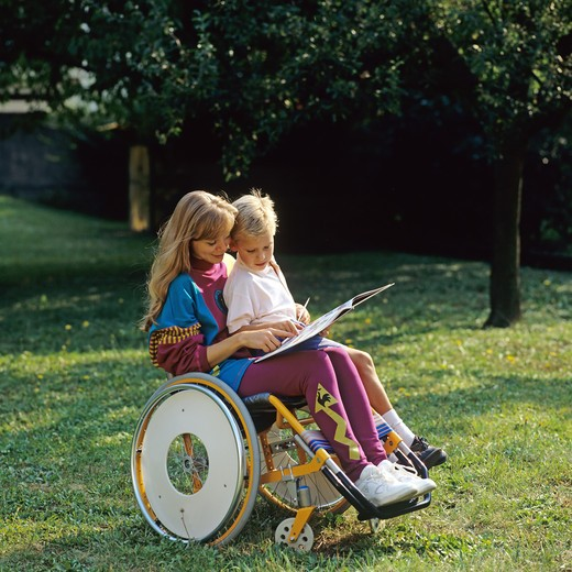 Stock Photo: 4285-10747 MR DISABLED WOMAN IN WHEELCHAIR READING TO LITTLE BOY ON LAP IN GARDEN