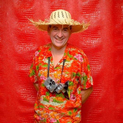 Stock Photo: 4285-10804 mr man with hawaiian shirt camera straw hat red background