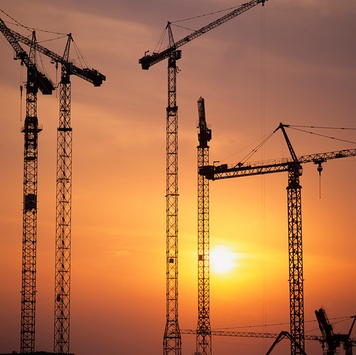 silhouettes of construction cranes on building site at sunset : Stock Photo
