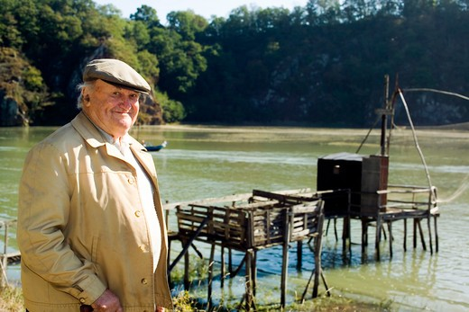 Stock Photo: 4285-12272 elderly man in front of a carrelet fishing hut at rance river brittany france