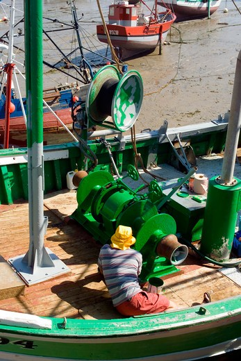 fisherman painting trawler fishing boat's winch with green paint at low tide erquy harbour brittany france : Stock Photo