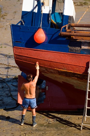 fisherman painting his trawler fishing boat erquy harbour brittany france : Stock Photo