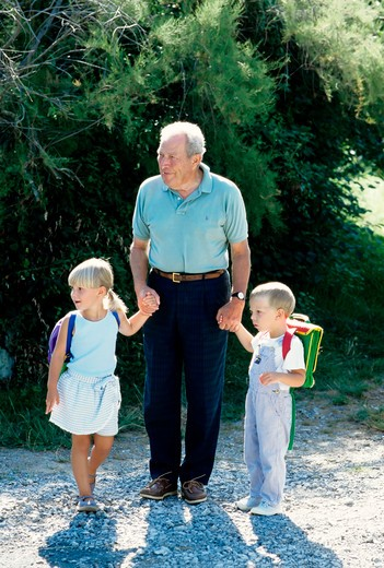 Stock Photo: 4285-13201 mr grandfather walking little boy and girl to school