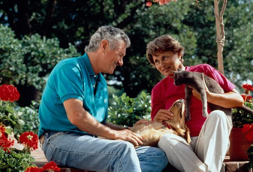 Stock Photo: 4285-1359 Senior couple sitting outside with pet dog and cat.