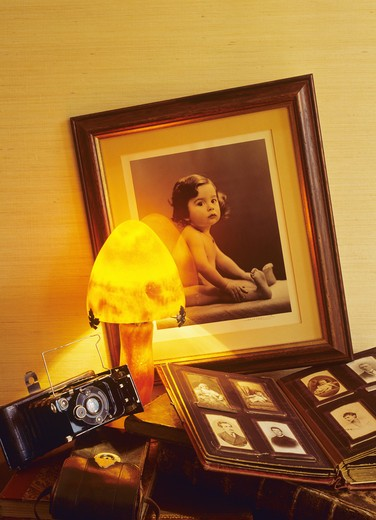 MR ANTIQUE PHOTO OF A BABY AND PICTURE ALBUM WITH FAMILY PORTRAITS AND ANCIENT FOLDING CAMERA AND GALLEE LAMP : Stock Photo