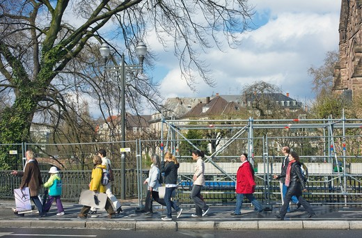Stock Photo: 4285-13799 GROUP OF PEOPLE WALKING IN FRONT OF FENCE AND SCAFFOLDING STRASBOURG ALSACE FRANCE