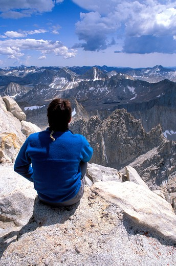 Climber looking out from the summit of Bear Creek Spire, John Muir Wilderness, Sierra Nevada Mountains, California : Stock Photo