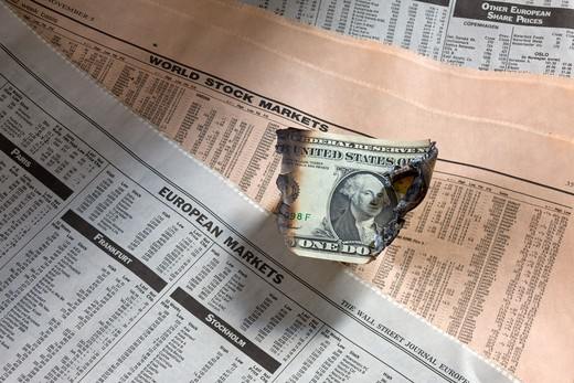 Stock Photo: 4285-14521 ONE BURNT US DOLLAR BILL ON FINANCIAL PAPERS