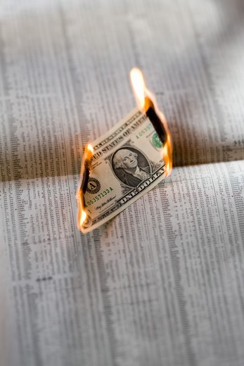 Stock Photo: 4285-14529 ONE US DOLLAR BILL BURNING ON FINANCIAL PAPER