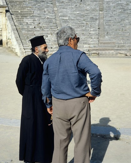 Stock Photo: 4285-14897 POPE ORTHODOX PRIEST AND MAN IN ANTIQUE THEATRE OF EPIDAURUS PELOPONNESE GREECE