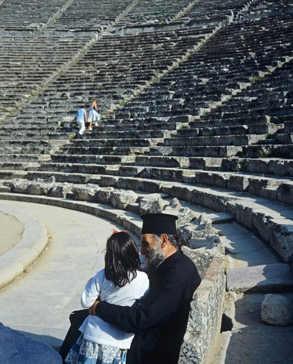 Stock Photo: 4285-14900 POPE ORTHODOX PRIEST WITH A LITTLE GIRL IN ANTIQUE THEATRE OF EPIDAURUS PELOPONNESE GREECE