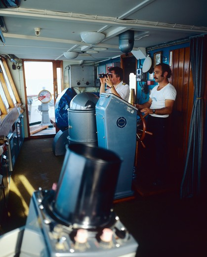 CAPTAIN LOOKING THROUGH BINOCULARS AND HELMSMAN IN BRIDGE OF A CRUISE SHIP GREECE : Stock Photo