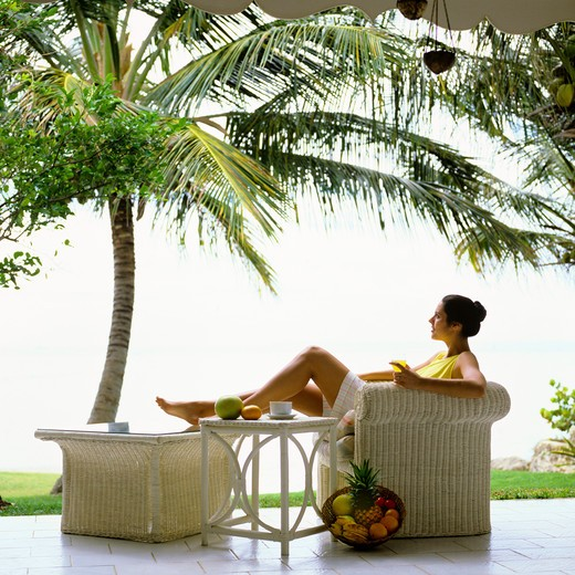 Stock Photo: 4285-15064 MR YOUNG WOMAN RELAXING IN WHITE ARMCHAIR TERRACE GUADELOUPE