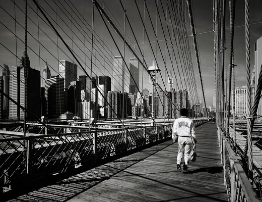 Stock Photo: 4285-15301 PRE 9/11 MAN WALKING ON BROOKLYN BRIDGE AND LOWER MANHATTAN SKYLINE NEW YORK USA