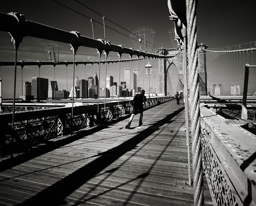 Stock Photo: 4285-15321 PRE 9/11 ROLLER SKATER ON BROOKLYN BRIDGE AND LOWER MANHATTAN SKYLINE NEW YORK USA