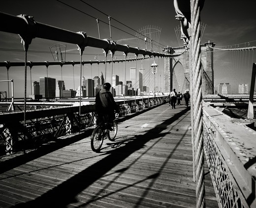 Stock Photo: 4285-15322 PRE 9/11 CYCLIST AND PEOPLE ON BROOKLYN BRIDGE AND LOWER MANHATTAN SKYLINE NEW YORK USA