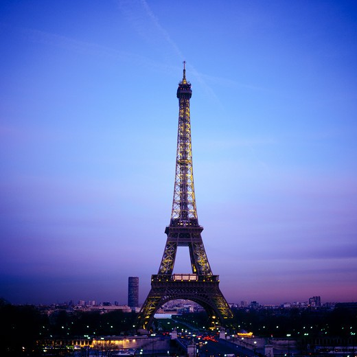 ILLUMINATED TOUR EIFFEL TOWER AT DUSK PARIS FRANCE : Stock Photo
