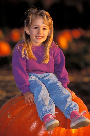 Stock Photo: 4285-2188 Child (age 3) sitting on a giant pumpkin at the Faulkner Farm, Santa Paula, California