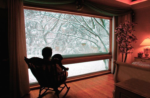 A man sitting with his dog in a rocking chair in front of a large picture window looking out at snow covered trees. : Stock Photo