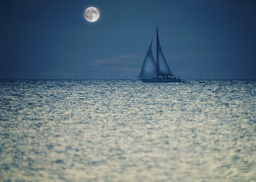 Two masted sailboat semi-silhouetted in shiny ocean at night with moon in background. : Stock Photo