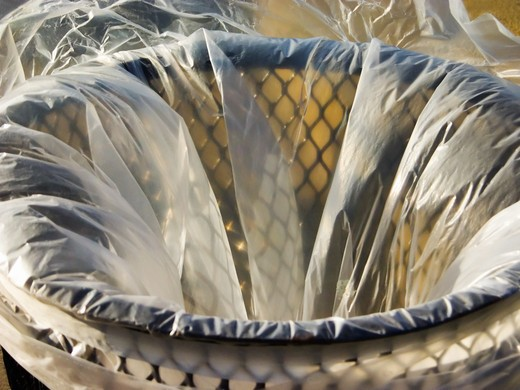 Stock Photo: 4285-3355 Trash metal wire basket with semi-clear plastic lining.