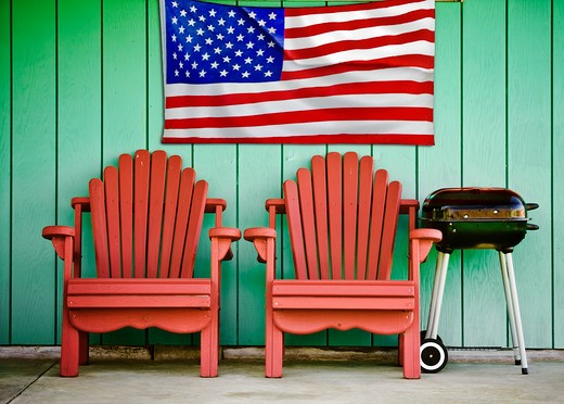 Stock Photo: 4285-3558 RED CHAIRS GREEN WALL, BARBECUE AND AMERICAN FLAG