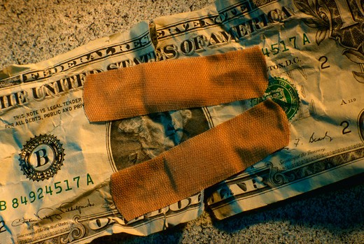 Torn dollar bill bandaged together. : Stock Photo
