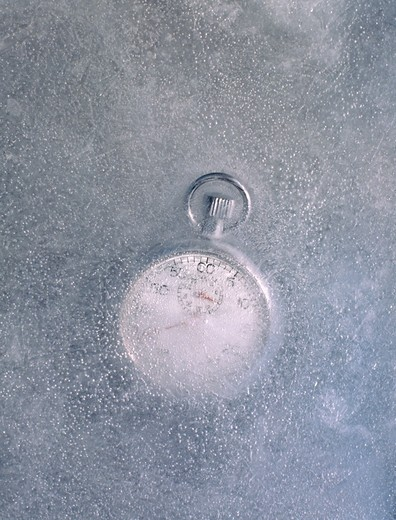 A stopwatch frozen in a block of ice signifying frozen time. : Stock Photo