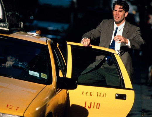 Businessman looking stressed as he gets out of a taxicab on a busy city street in New York City. : Stock Photo