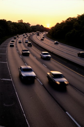 Cars traveling on a freeway in the early evening as the yellow sun sets behind them. : Stock Photo