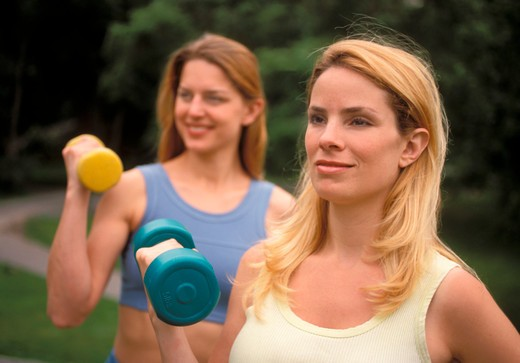 Stock Photo: 4285-4073 Two women excerising with weights outdoors.