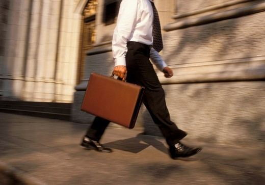 Stock Photo: 4285-4074 Businessman with briefcase walking on a city street.